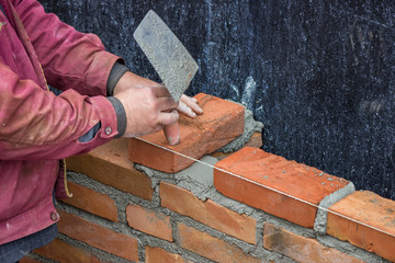 Builder worker with trowel laying solid clay brick