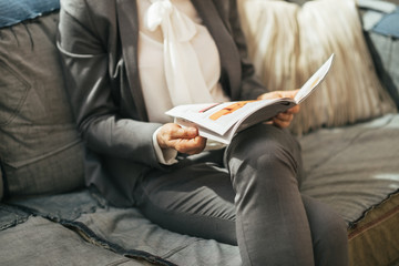 Closeup on business woman reading magazine