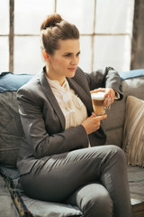 Business woman with coffee latte sitting on divan