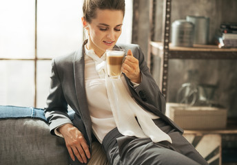 Portrait of happy business woman drinking coffee latte