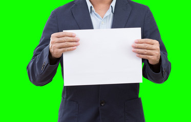Business man holding blank paper isolated on green  background