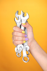 Female hand with stylish colorful nails holding wrench,
