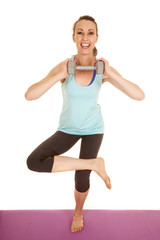 woman fitness blue tank barefoot one leg hold weight