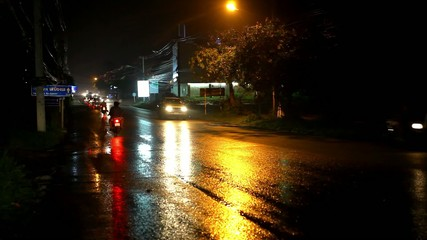 Cars and motorbikes driving on wet road at night after rain