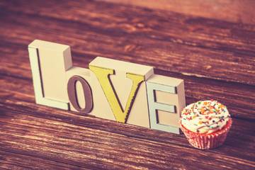 Cupcake and word Love on wooden table.