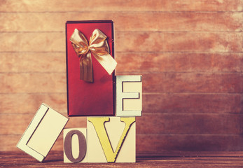 Little gift and word Love on wooden table.
