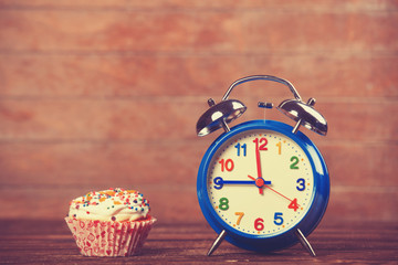 cupcake with alarm clock on wooden table.