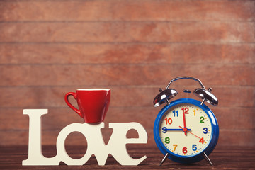 Word Love, cup and alarm clock on wooden table.