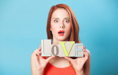 Surprised redhead women with word Love on blue background.