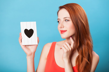 Redhead women with frame on blue background.