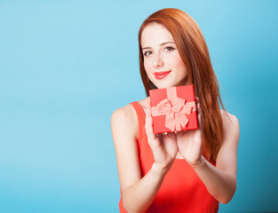 Smiling redhead women with gift on blue background.