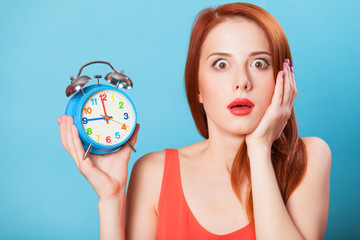 Surprised redhead women woth alarm clock on blue background.