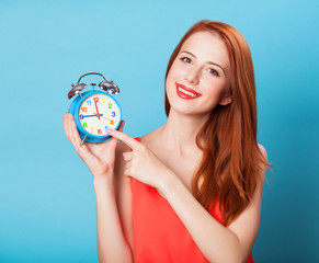 Smiling redhead women woth alarm clock on blue background.