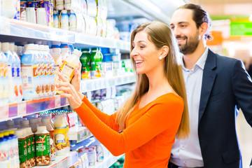 Paar wählt Milchprodukte im Supermarkt Kühlregal