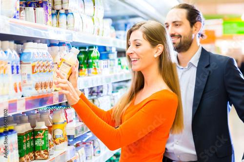 Paar wählt Milchprodukte im Supermarkt Kühlregal - 66627802