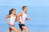 Running couple jogging on beach