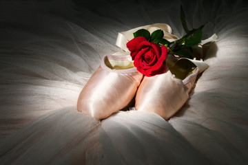 Old used ballet slippers lying on floor with rose and tutu