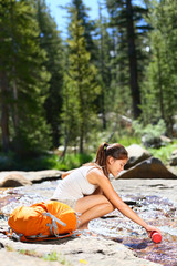 Hiking woman drinking water in river in Yosemite