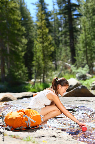 Hiking woman drinking water in river in Yosemite