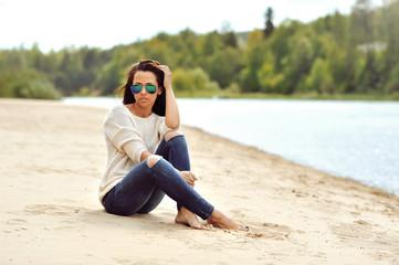 Sexy brunette woman sitting on a beach