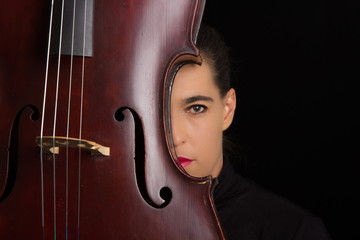 Beautiful brunette holding cello with selective light in black d