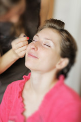 Bride applying wedding make-up by professional make-up artist