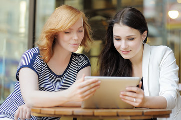 Two girls using tablet computer