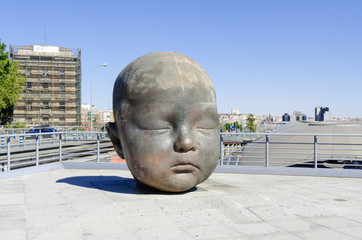 Giant baby head sculpture in Atocha Madrid Spain