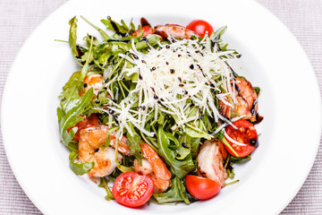 Salad with arugula and shrimps in a white plate