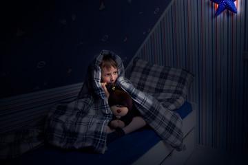 Kind versteckt sich unter der Decke