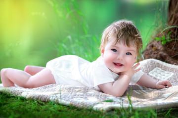 Happy little baby having fun in the park on the lake shore backg