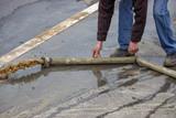 Fototapety Man pumping away flood water 2
