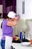 Cook wiping her brow as she does washing up