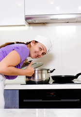 Smiling cook bending over a pot on the stove