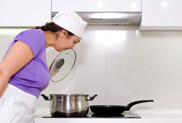 Female cook watching a pot boil