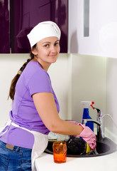 Smiling woman cook cleaning dishes