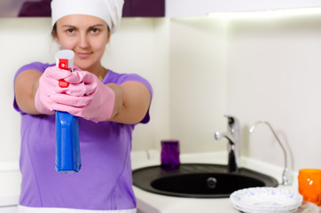 Playful housewife taking aim with the detergent