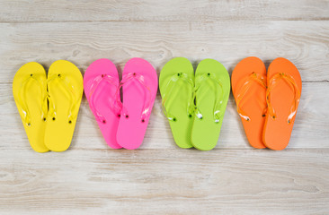 Four pairs of New Sandals on faded white wood