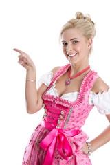 Frau im rosaroten Dirndl isoliert zeigt mit dem Zeigefinger