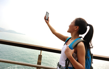 woman hiker use cell phone taking photo on seaside