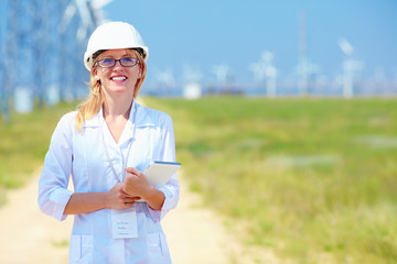 young female researcher analyzes readouts on wind power station