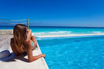 Gorgeous woman sunbathing near swimming pool