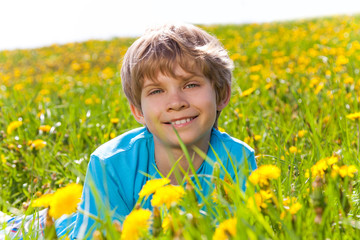Smiling boy in dandelions portrait