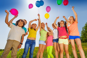 Kids stand in half round with arms up to balloons