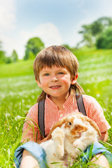 Small boy hugging rabbit in green field