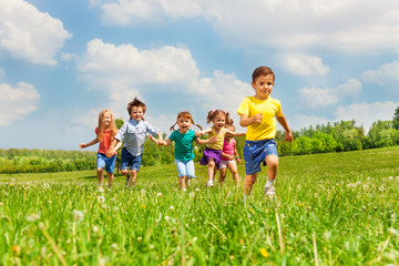 Running kids in green field during summer