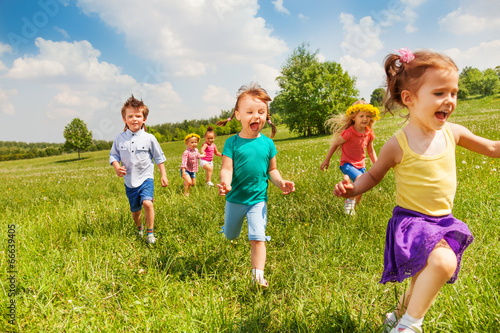 Excited running kids in green field play together - 66639405
