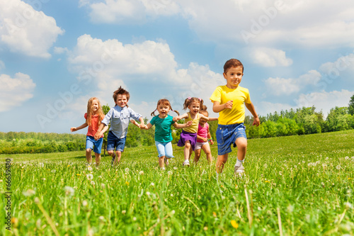 Running kids in green field during summer - 66639480
