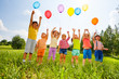 Leinwanddruck Bild - Happy kids with balloons and arms up in the sky