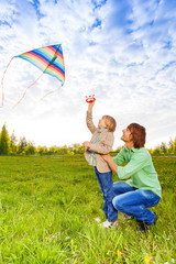 Father holds kid while watching flying kite
